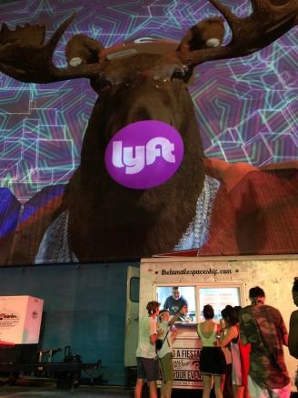 A photo of a moose with the Lyft logo and people waiting in line for tacos.